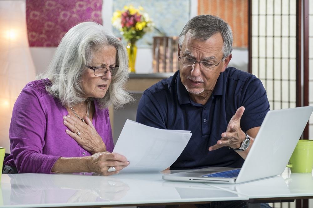 Frustrated Senior Couple Looking at Home Title Paperwork