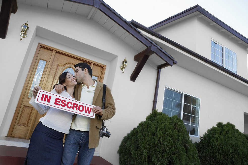 Couple Holding Escrow Sign