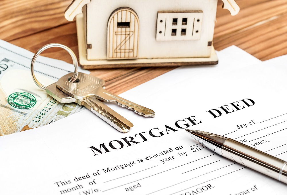 Mortgage Deed with Keys and House Model on Table